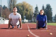 Gli sport coppia l'allungamento del corpo nel parco Immagine Stock Libera da Diritti