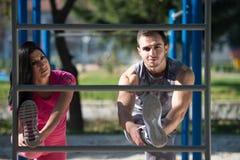 Gli sport coppia l'allungamento del corpo nel parco Fotografie Stock Libere da Diritti