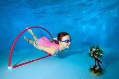 Gli sport dei giochi da bambini subacquei Tuffi e nuotate attraverso il cerchio al fondo dello stagno immagini stock