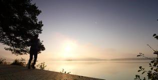 Gli sport equipaggiano il controllo del tempo sul suo orologio sportivo Corridore nel lago della montagna che si esercita contro  archivi video