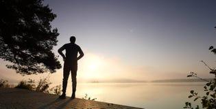 Gli sport equipaggiano il controllo del tempo sul suo orologio sportivo Corridore nel lago della montagna che si esercita contro  video d archivio