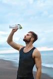 Gli sport equipaggiano l'acqua di versamento sopra il fronte dopo l'allenamento alla spiaggia Immagini Stock
