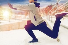 Gli sport equipaggiano l'allungamento della gamba a recintano l'inverno Fotografie Stock Libere da Diritti