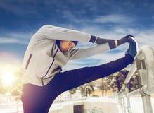 Gli sport equipaggiano l'allungamento della gamba a recintano l'inverno Fotografia Stock Libera da Diritti