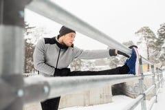 Gli sport equipaggiano l'allungamento della gamba a recintano l'inverno Fotografie Stock