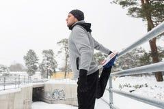 Gli sport equipaggiano l'allungamento della gamba a recintano l'inverno Immagini Stock