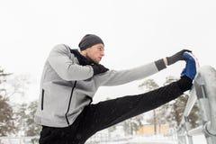 Gli sport equipaggiano l'allungamento della gamba a recintano l'inverno Fotografia Stock