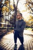 Gli sport equipaggiano l'allungamento delle gambe dopo avere corso Stagione di autunno Fotografia Stock Libera da Diritti
