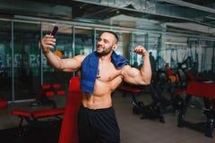 Gli sport equipaggiano la presa del selfie Culturista con l'asciugamano dopo un allenamento Atleta su un fondo vago della palestr Fotografia Stock Libera da Diritti