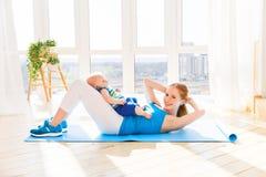Gli sport generano è impegnato nella forma fisica e nell'yoga con il bambino a casa immagine stock