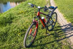 Gli sport vanno in bicicletta su un'erba verde vicino ad un lago della città Fotografia Stock