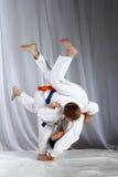 Gli sportivi con una cinghia blu ed arancio stanno facendo i tiri di judo Fotografia Stock