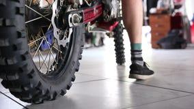 Gli sportivi maschii lascia il garage al suo motociclo di enduro stock footage