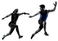 Gli sprinter dei corridori di relè di atletica che eseguono i corridori hanno isolato il silho Fotografie Stock