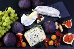 Gli spuntini dell'insieme dell'assortimento per vino su uno scisto imbarcano: camembert del formaggio o Brie, blu di Dor del form fotografia stock libera da diritti