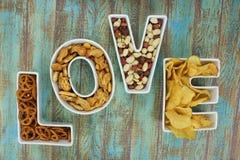 Gli spuntini nell'amore hanno modellato le ciotole della lettera su fondo rustico Immagine Stock