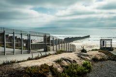 Gli Stati Uniti confinano la parete con il Messico che incontra l'oceano Pacifico nella California immagini stock libere da diritti