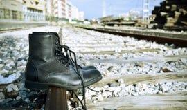 Gli stivali degli uomini abbandonati sui binari ferroviari Fotografie Stock Libere da Diritti
