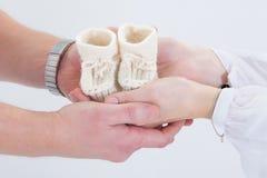 Gli stivali del bambino in mani dei genitori. Immagini Stock