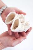 Gli stivali del bambino in mani dei genitori. Immagine Stock