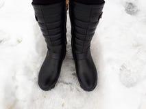 Gli stivali delle donne di colore nella neve fotografia stock