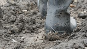 Gli stivali di gomma degli uomini in terra bagnata fangosa sporca video d archivio