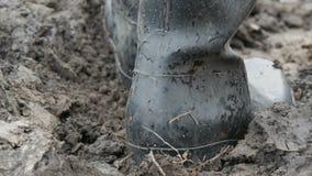 Gli stivali di gomma degli uomini in terra bagnata fangosa sporca stock footage