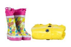 Gli stivali di gomma e l'eleganza piovono il giallo del rivestimento per la ragazza Bianco isolato fotografia stock