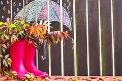 Gli stivali di gomma (rainboots) e le foglie autunnali sono sui precedenti di legno con l'ombrello del disegno Fotografie Stock
