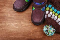 Gli stivali ed il cappello dei bambini di inverno sul backgroun strutturato di legno Fotografia Stock