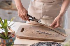 Gli strati di taglio dell'artista di vetro macchiato nel piccolo mosaico quadra Primo piano fotografia stock libera da diritti