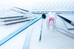 Gli strumenti del dentista, il grafico di eruzione di dente ed il dente modellano sulla tavola con la tastiera di computer e sond immagine stock libera da diritti