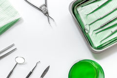 Gli strumenti del dentista si chiudono su sul modello bianco di vista superiore del fondo dello scrittorio dell'ospedale Fotografia Stock Libera da Diritti