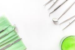 Gli strumenti del dentista si chiudono su sul modello bianco di vista superiore del fondo dello scrittorio dell'ospedale Fotografia Stock