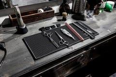 Gli strumenti della bugia del barbiere su una stuoia nera sul desktop immagine stock libera da diritti