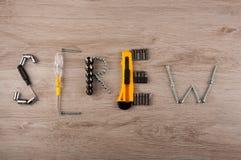 Gli strumenti della riparazione risiedono nella vite di parola sulla tavola di legno Fotografie Stock