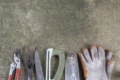 Gli strumenti di giardinaggio, la pala, i guanti, tagli, hanno visto sul pavimento di calcestruzzo Fotografia Stock Libera da Diritti