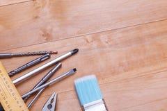 Gli strumenti ed i trapani non sono indicati completamente su un fondo di legno Vista da sopra fotografie stock