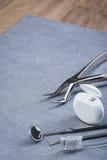 Gli strumenti, il filo di seta e la spazzola dentari di base su grey sorgono Immagini Stock Libere da Diritti