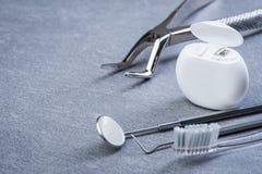 Gli strumenti, il filo di seta e la spazzola dentari di base su grey sorgono Immagini Stock