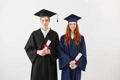 Gli studenti allegri si laurea i diplomi sorridenti della tenuta che esaminano la macchina fotografica Priorità bassa bianca Immagini Stock