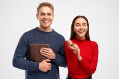 Gli studenti amichevoli allegri, si divertono insieme, tengono il taccuino marrone I modelli controllano il fondo bianco in studi fotografia stock