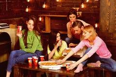 Gli studenti, amici, compagni del gruppo con l'insegnante celebrano, si divertono, fondo interno di legno scuro Partito della piz immagini stock libere da diritti