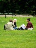 Gli studenti approfittano del tempo per pranzare sull'erba di un giardino pubblico e per rivedere i loro corsi per il baccalaurea Immagini Stock Libere da Diritti