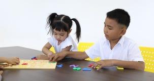 Gli studenti asiatici giocano insieme il puzzle dell'alfabeto archivi video