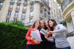 Gli studenti che godono con la compressa vicino alla costruzione dell'università ed imparano Immagine Stock