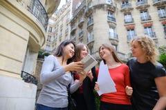 Gli studenti che godono con la compressa vicino alla costruzione dell'università ed imparano Fotografie Stock