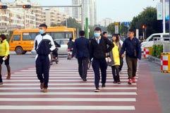 Gli studenti cinesi della scuola secondaria attraversano la strada ed indossano le maschere Fotografia Stock