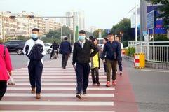 Gli studenti cinesi della scuola secondaria attraversano la strada ed indossano le maschere Fotografia Stock Libera da Diritti