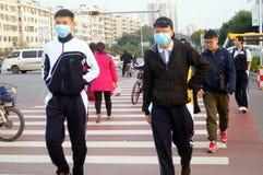 Gli studenti cinesi della scuola secondaria attraversano la strada ed indossano le maschere Fotografie Stock Libere da Diritti